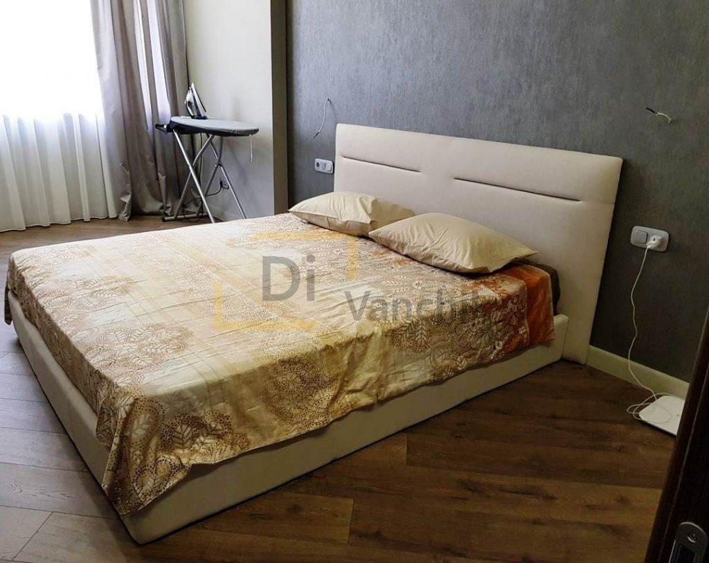 бежевая мягкая кровать со спинкой