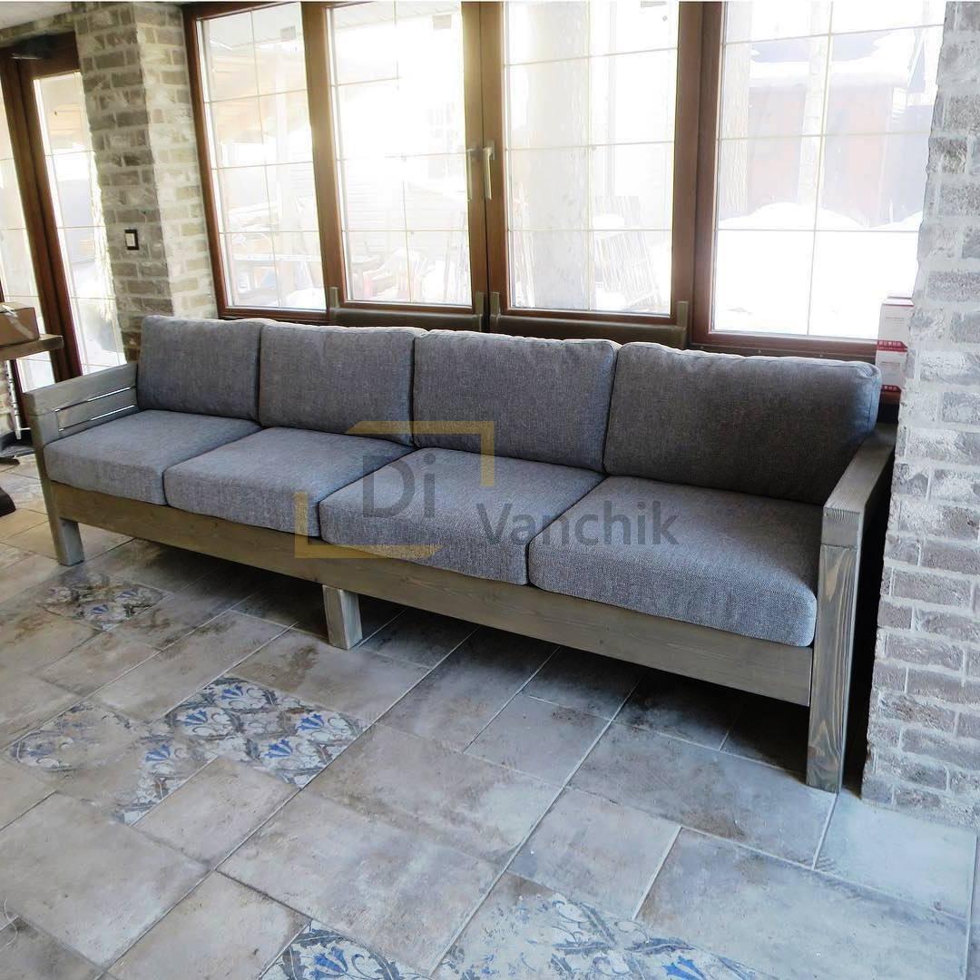 диван у окна на деревянном каркасе
