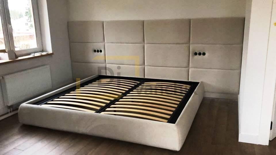 мягкая кровать с большой спинкой на стене